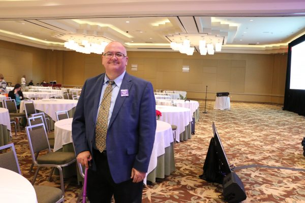 man standing in a hotel conference room with a cane
