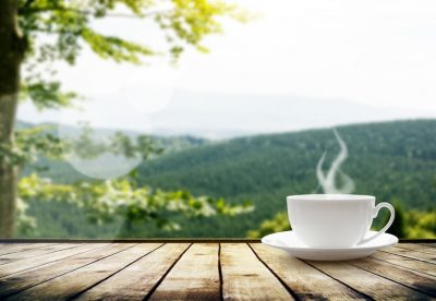 38234007 - cup with tea on table over mountains landscape with sunlight. beauty nature background